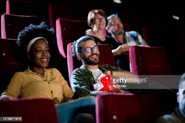 couple watching a comedy film and enjoying their date at the cinema - film stock pictures, royalty-free photos & images
