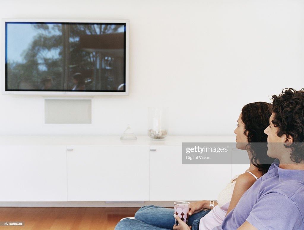 Couple Watching a Flat Screen TV in Their Home : Stock Photo