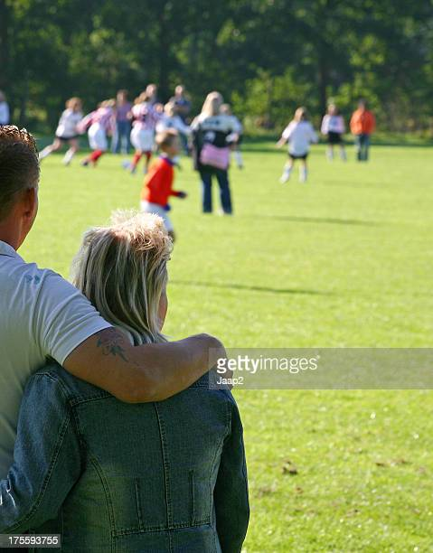 Couple watching a game of soccer from the sideline