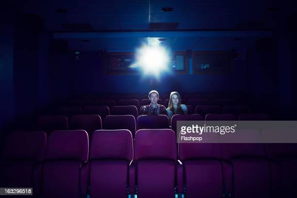 couple watching a movie in an empty cinema - industrie du cinéma photos et images de collection