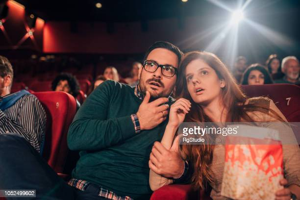 Couple watching a movie in fear