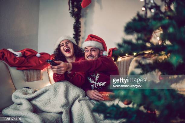 couple watching a movie on christmas eve in bed - film stock pictures, royalty-free photos & images