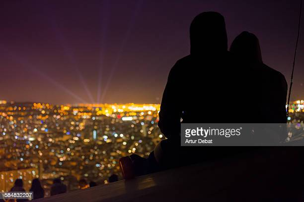 Couple watching Barcelona cityscape from the hill