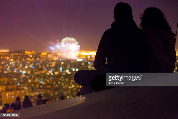 Couple watching Barcelona fireworks from hill