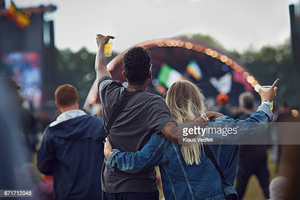 Couple watching concert & holding beers, rear view