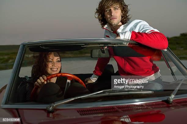couple watching drive-in movie in parked convertible - autokino stock-fotos und bilder