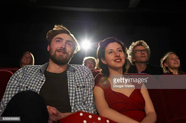 Couple watching film in movie theatre.