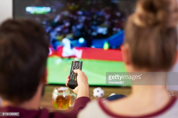 couple watching football match on tv - match sportivo foto e immagini stock