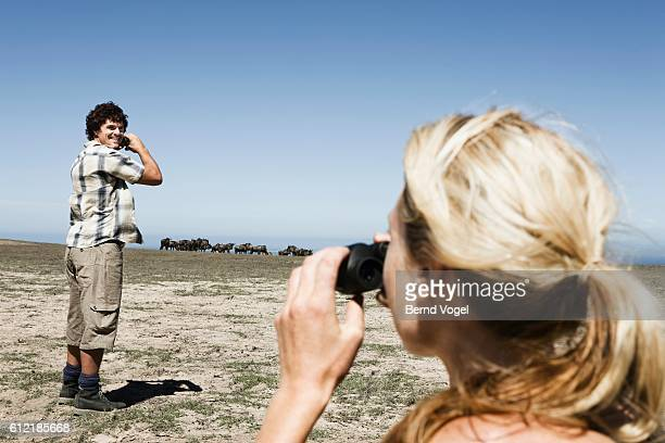 Couple Watching Herd of Wildebeests
