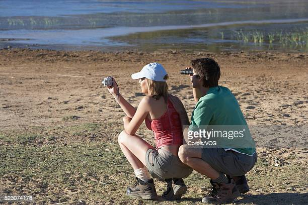 Couple Watching Hippos at Water Hole