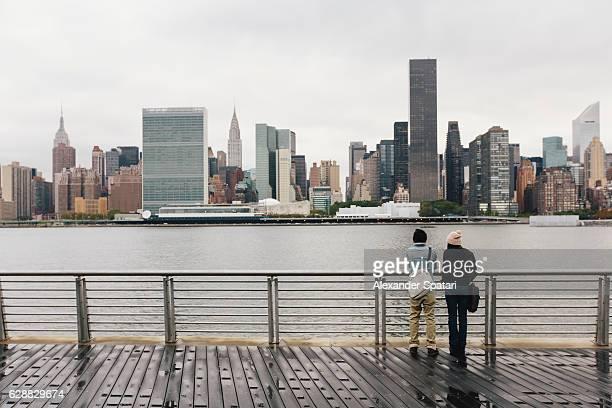 Couple watching Manhattan skyline, New York City, NY, USA