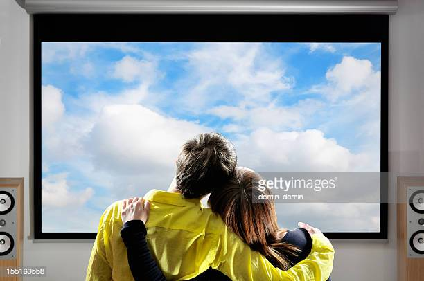 Couple watching movies on large screen, home theater system
