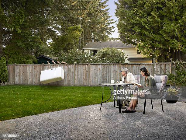 couple watching refrigerator being thrown into their yard - frigo humour photos et images de collection
