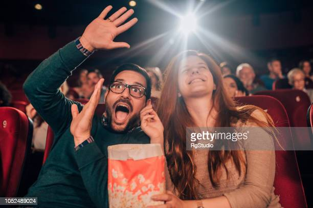 Couple watching scary movie in the cinema