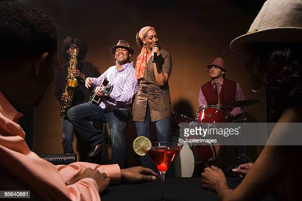 Couple watching singer and band performing jazz in nightclub