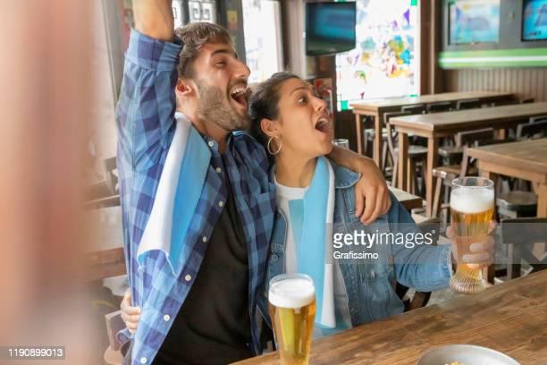 pareja viendo partido de fútbol en tv bebiendo cerveza en el pub - bandera argentina fotografías e imágenes de stock