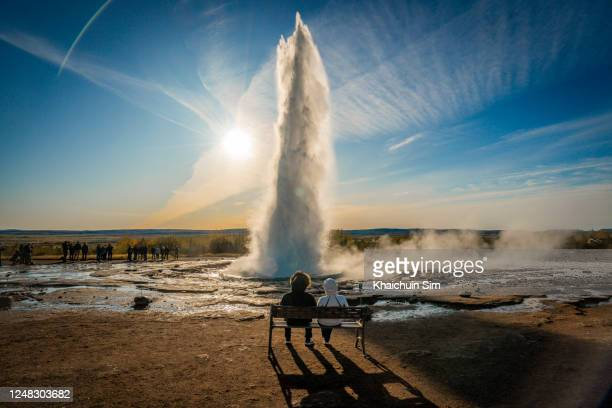 couple watching strokkur hot geyser at haukadalur valley - iceland stock pictures, royalty-free photos & images
