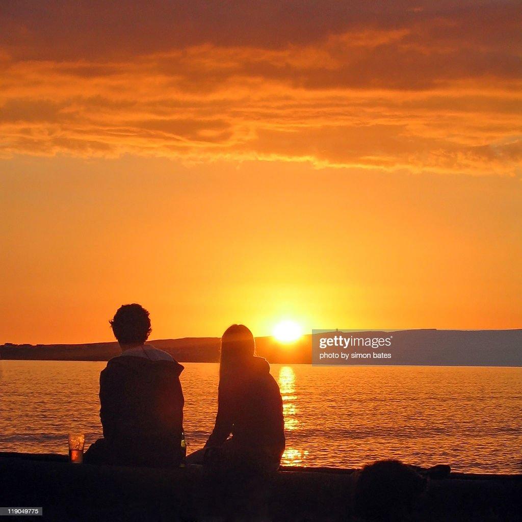 Couple Watching Sunset At Beach Stock Photo