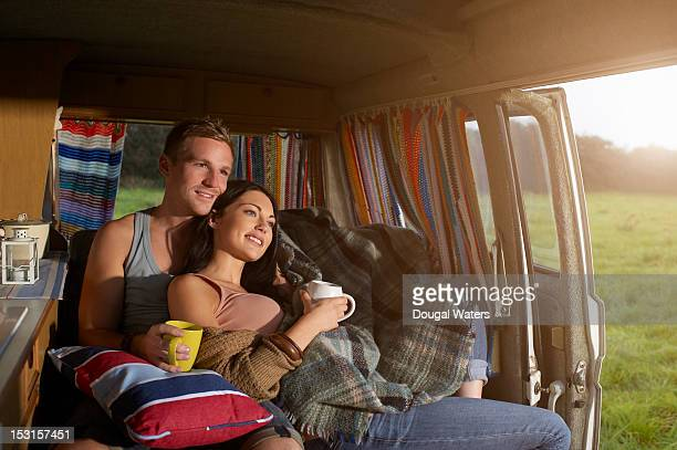 Couple watching sunset from camper van.