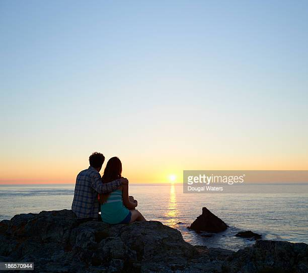 Couple watching sunset from UK coast.