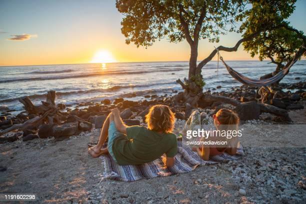 paar beobachtet sonnenuntergang am strand - erschwinglich stock-fotos und bilder