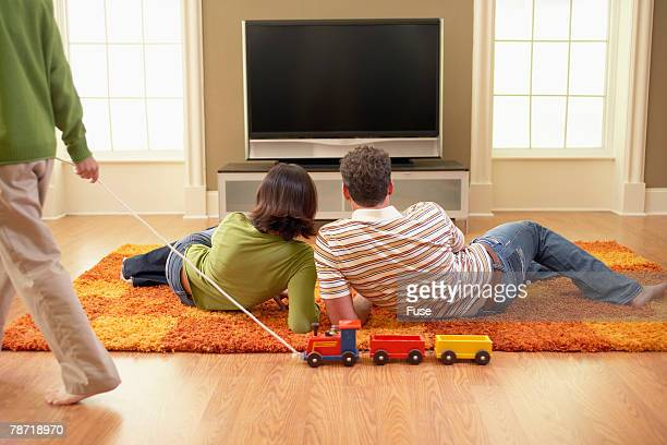 couple watching television and son pulling toy train - 大型テレビ ストックフォトと画像