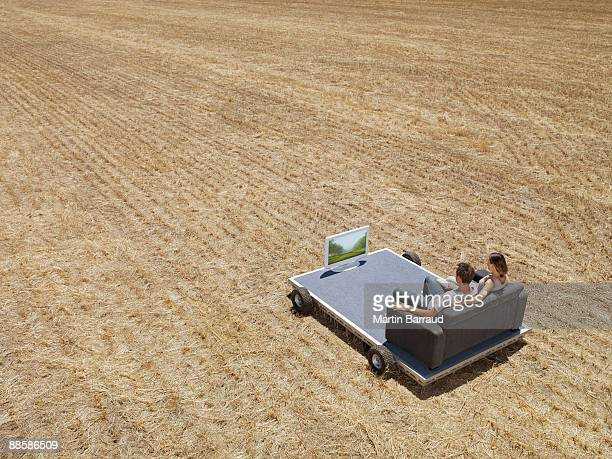 Couple watching television in field
