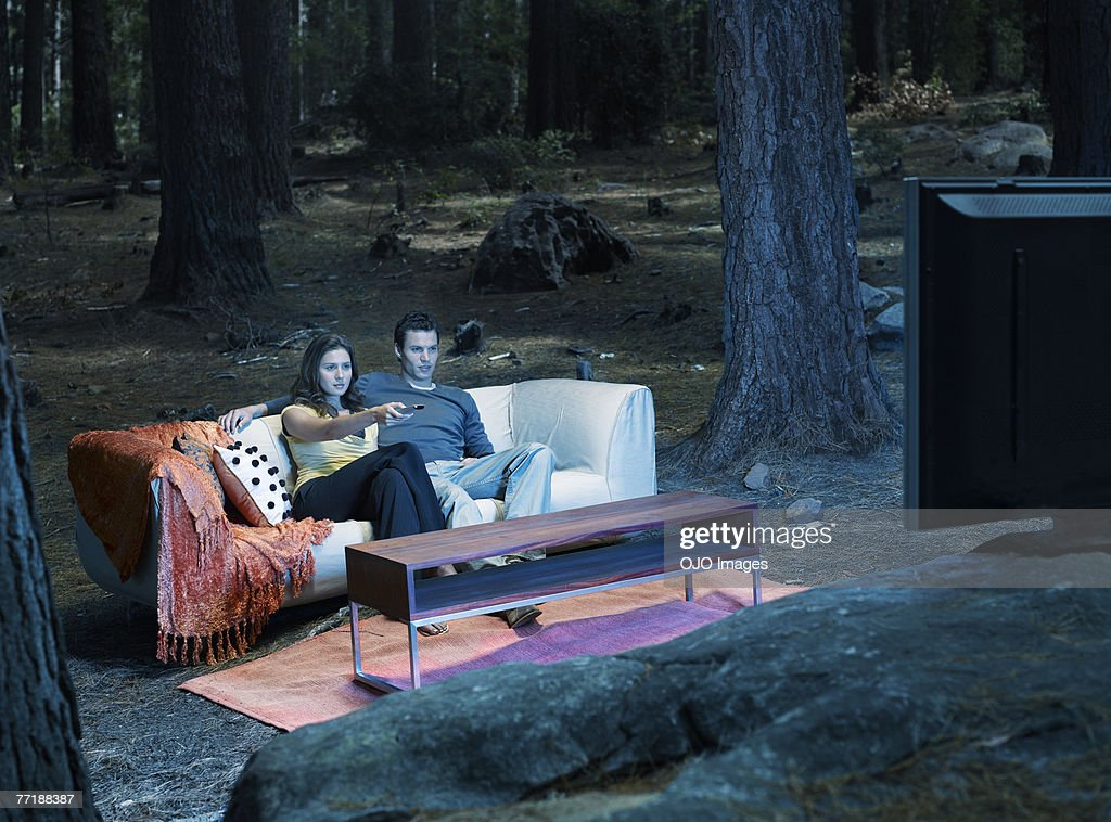 A couple watching television outdoors in the woods : Stock Photo