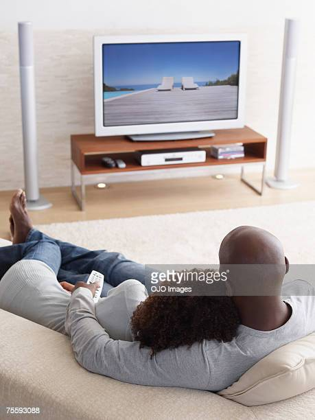 A couple watching television relaxing