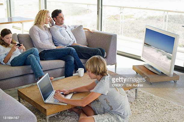 couple watching television set while their children busy in different activities - familia de dos generaciones fotografías e imágenes de stock
