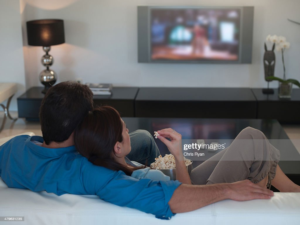 Couple watching television together and eating popcorn : Stock Photo