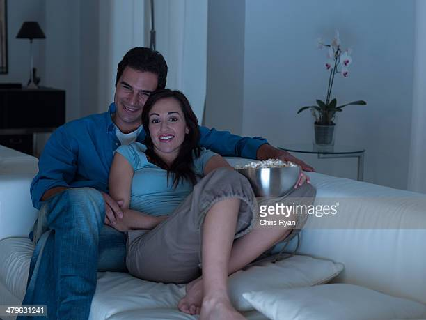 Couple watching television together and eating popcorn