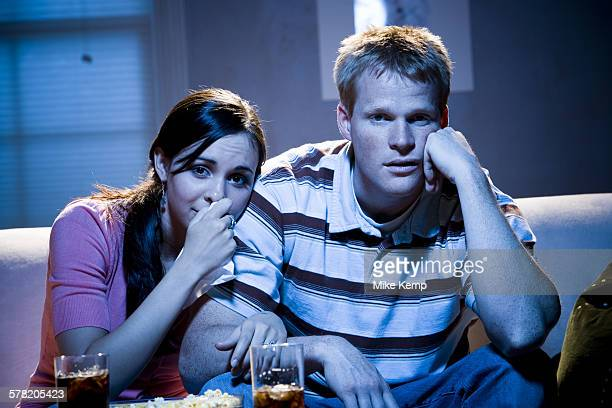 Couple watching television with bowl of popcorn looking sad