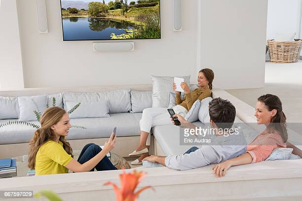 Couple watching television with their daughters busy in different activities