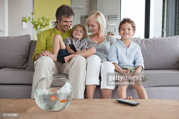 Couple watching television with their sons