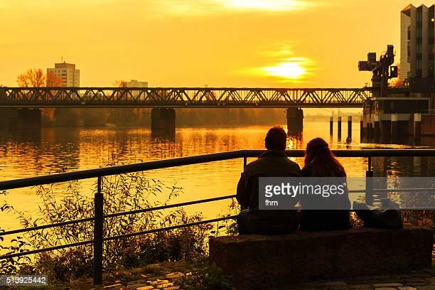 Couple watching the romantic sunset near Main river in Frankfurt/ Main, Germany