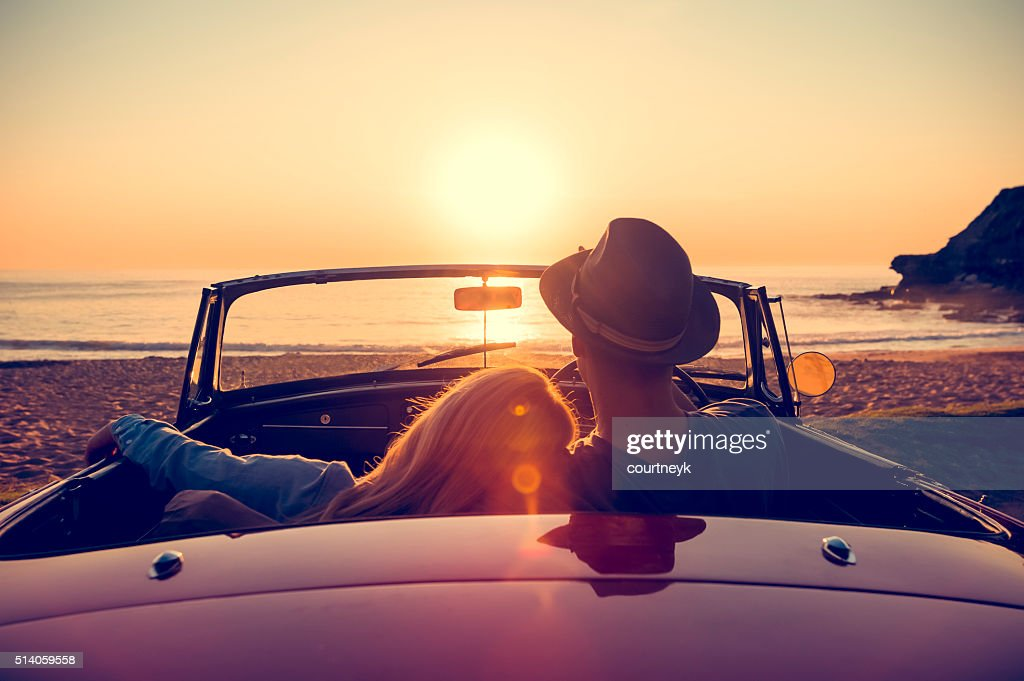 Couple watching the sunset in a convertible car. : Stock Photo