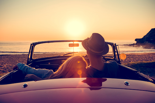 Couple watching the sunset in a convertible car. - gettyimageskorea