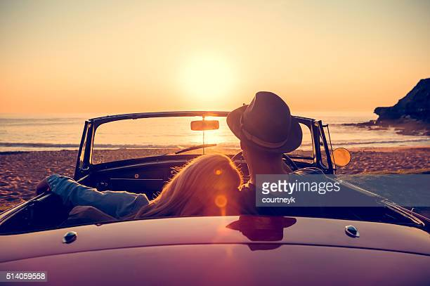 couple en regardant le coucher de soleil dans une décapotable. - amour photos et images de collection
