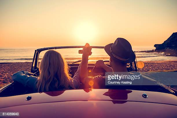 Couple watching the sunset in a convertible car.