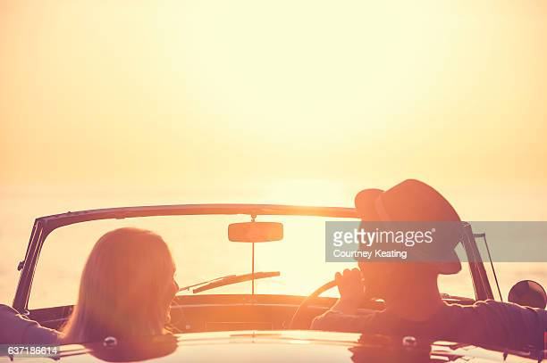 Couple watching the sunset in a convertible car