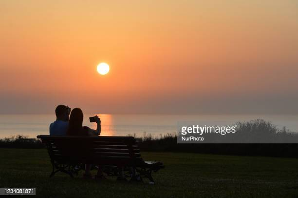 Couple watching the sunset near Arromanches. On Wednesday, July 20 in Arromanches, Calvados, Normandy, France.