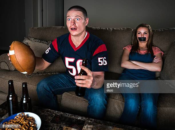 couple watching TV football - shocked guy and bored girl