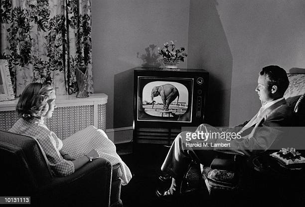 COUPLE WATCHING TV IN 1955 LIVING ROOM