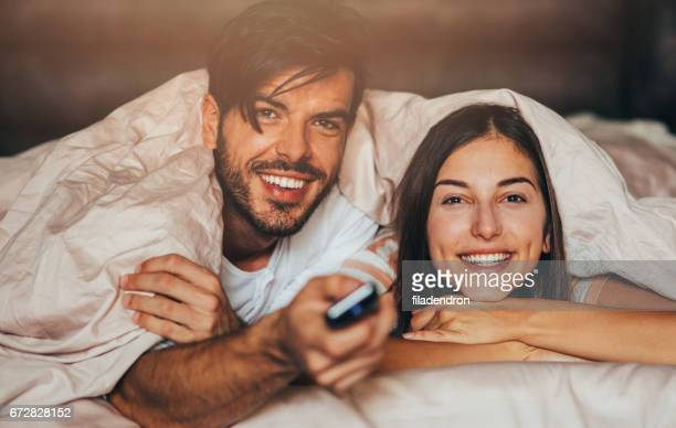 couple watching tv in bed - television show stock pictures, royalty-free photos & images