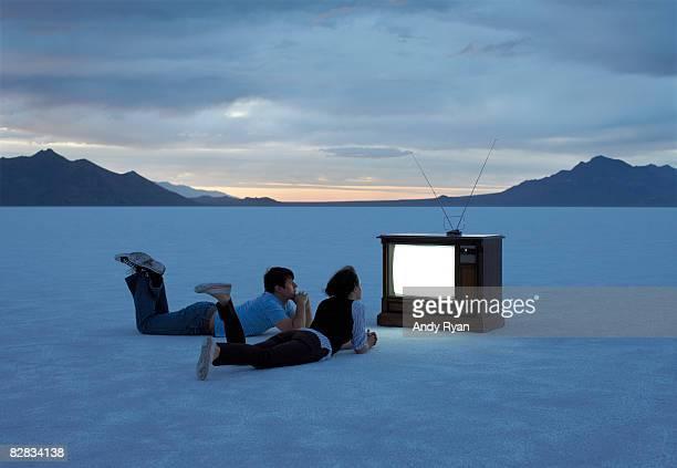 couple watching tv on salt flats at dusk. - sólo con adultos fotografías e imágenes de stock