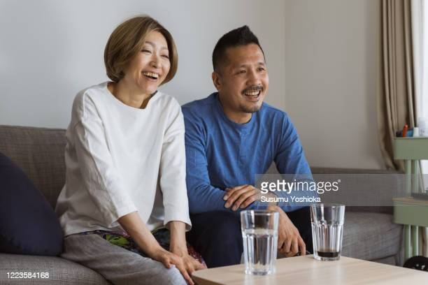 couple watching tv on sofa - 中年カップル ストックフォトと画像