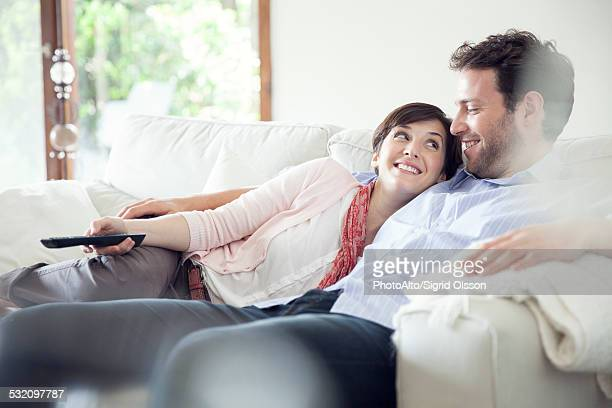 Couple watching TV together on sofa