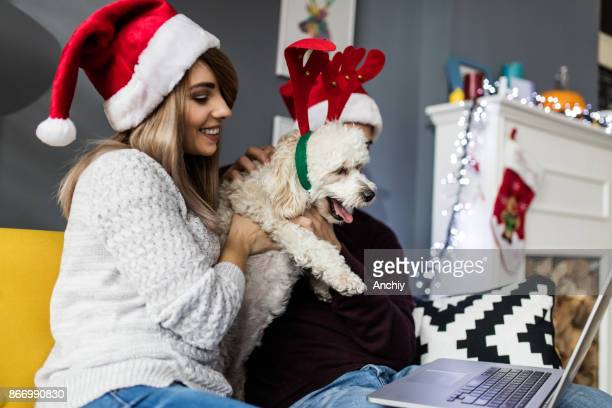 couple watching video with their dog on laptop, christmas concept.