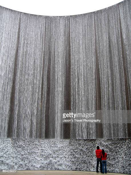 Couple watching water wall, rear view